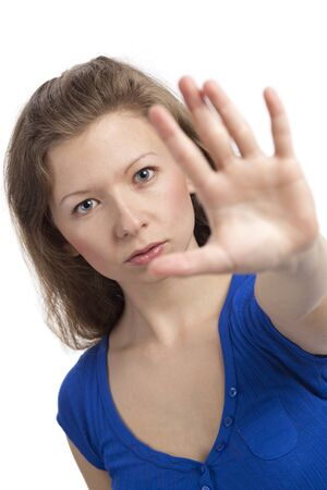 Serious young woman with hand raised to stop photo