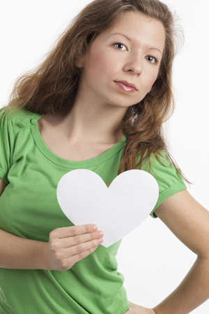 dispassionate: Woman with serious look holding white heart in one hand