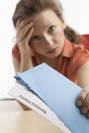 Young woman with the letter of termination looks desperately photo