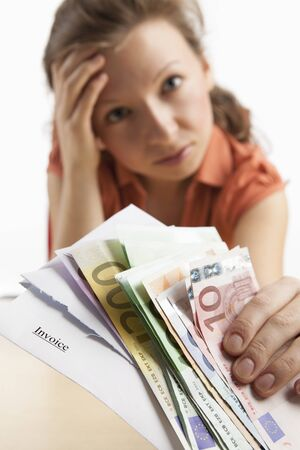 Young, desperate-looking woman holding euro notes and invoice in the camera