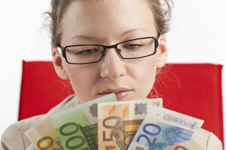 Young woman looks at a fan of money photo