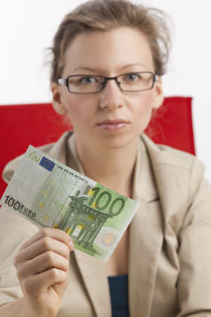 monetary devaluation: Young woman with a serious look is holding a hundred euro note