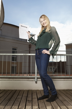 lodger: Young woman on the balcony proudly showing her tenancy agreement