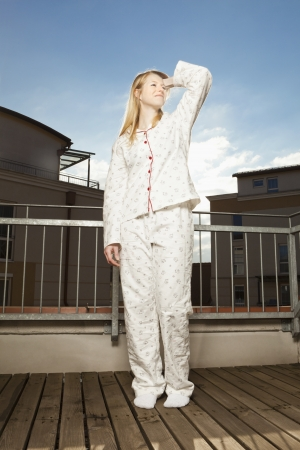 Young woman in pajamas stands on the balcony and enjoys the sunshine photo