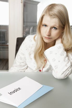 Young woman in her apartment with invoice on the table Stock Photo - 16661524