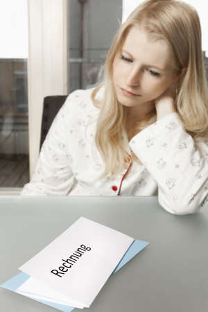 Young woman in her apartment looks dejected on invoice