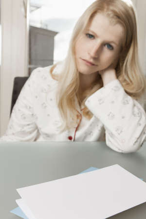 Letter paper with copyspace in front of woman with downcast glance Stock Photo - 16661506