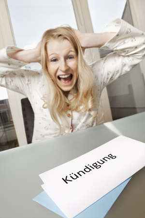 termination: Screaming woman sitting in her apartment and receives letter of termination