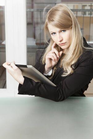 business skeptical: Mirada esc�ptica de una mujer de negocios con PC de la tableta