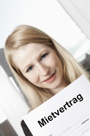 Young blonde woman holding rental agreement