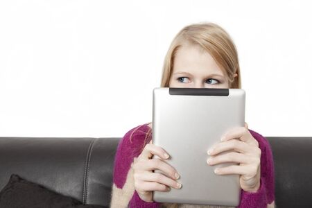 Side view of a woman holding a tablet PC in front of her face photo