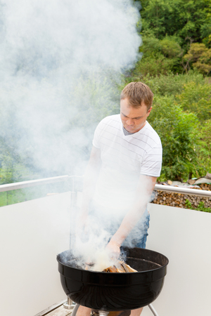 griller: Grill master when igniting the fire of the grill Stock Photo