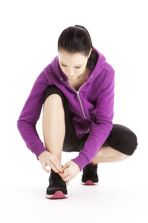 forerunner: Active Sportswoman binds her shoes Stock Photo