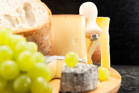 cheese plate: Cheese plate with wine grapes and white bread Stock Photo