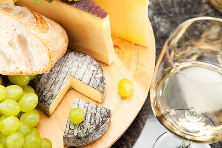 White wine with cheese platter grapes and white bread photo