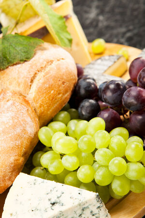 cheese plate: Cheese plate with red and green wine grapes Stock Photo