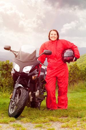 rainwear: Motorcycle rider puts on rain protection