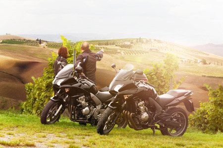 Two motorcyclists enjoying the view in Tuscany