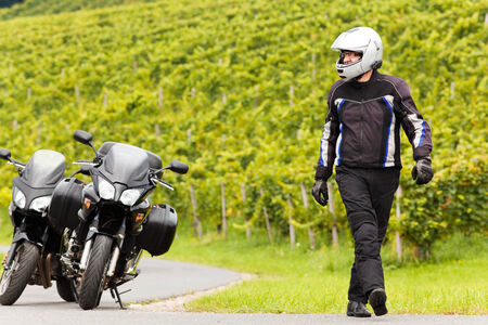 Motorcyclist with helmet walkes on the road
