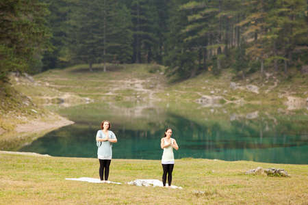 Two women doing yoga exercise in front of a lake photo