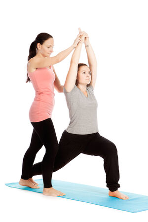 posture correction: Yoga teacher provides assistance in training Stock Photo