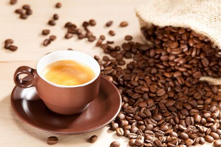 intense flavor: A cup of coffee and roasted coffee beans