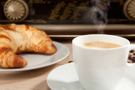 Listening to the radio at breakfast with coffee and croissant Stok Fotoğraf
