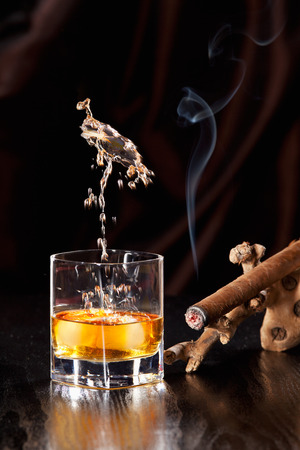 whisky glass: Fallen ice cubes causing a splash in the Whisky glass Stock Photo