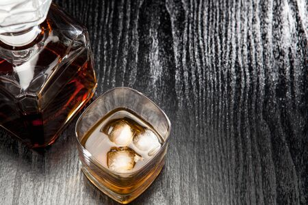 Alcohol in glass with ice cubes and a carafe