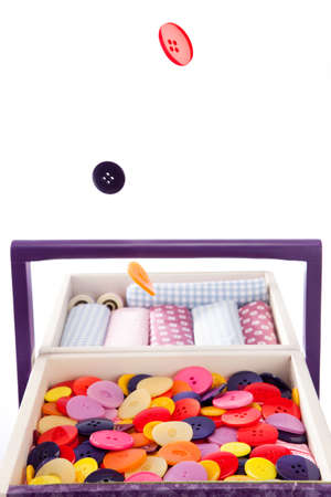 sewing box: Colorful buttons fall into a sewing box Stock Photo