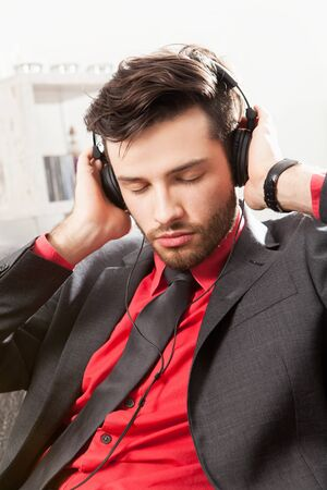 Man in suit listening to music with headphones photo