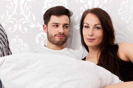 Young couple snuggling in bed photo