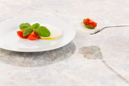 deliberately: Mozzarella salad with tomatoes and basil on a fork Stock Photo