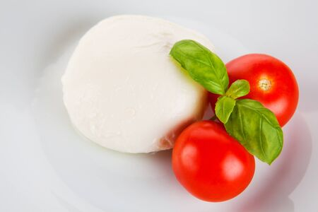 Tomatoes, mozzarella and basil on plate