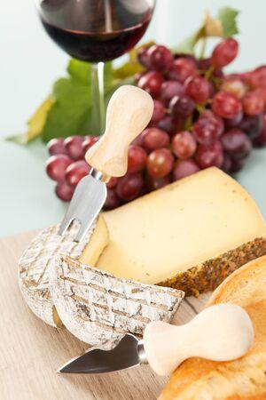 tabla de quesos: Vino y uvas con plato de queso y baguette Foto de archivo