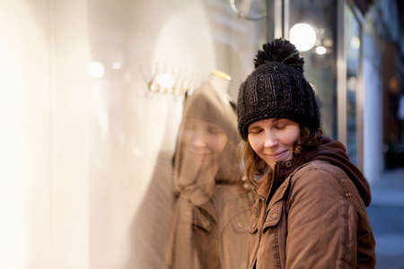 soulfulness: Happy woman leans on the lighted storefront Stock Photo