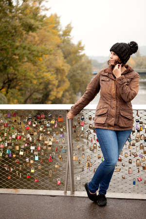 lovesickness: Woman stands waiting at the bridge railing with locks of lovers Stock Photo