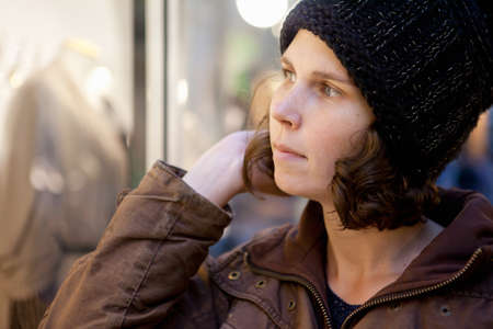 skepticism: Woman looks pensively into the storefront Stock Photo
