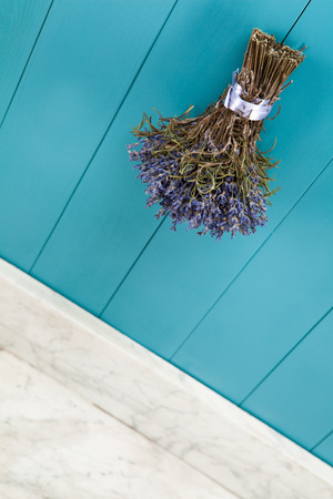 hanging up: A bunch of lavender hanging up to dry on a Mediterranean blue wooden wall Stock Photo