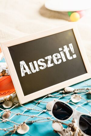 auszeit: Beach with holiday gear and a board with the word Auszeit
