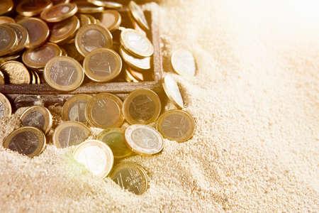 euro coins: Euro coins on a sunny sandy beach