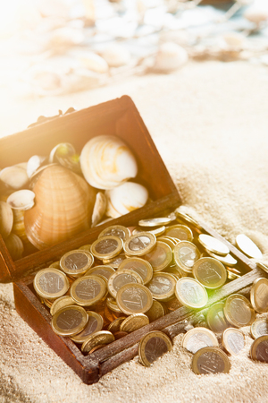 euro coins: Treasure chest on a sandy beach, filled with Euro coins