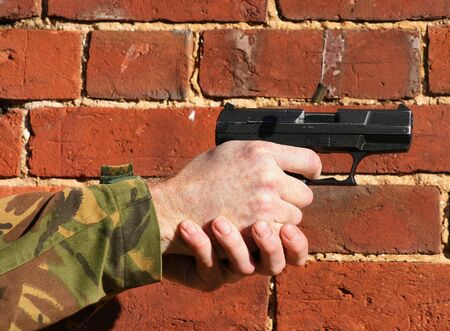 being the case: A 9mm Pistol being fired with  ejected case in the air this is against a brick wall with just the hand and some sleeve showing with room for text
