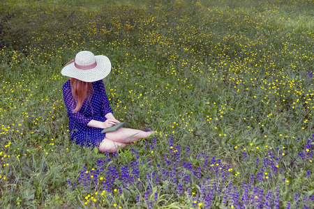 Girl in blue dress and white hat ,sitting on the grass, holding a sketchbook.