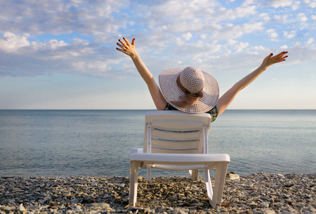 young girl in a hat lying on a sun lounger with her hands up, enjoys life, the view from the back. Reklamní fotografie