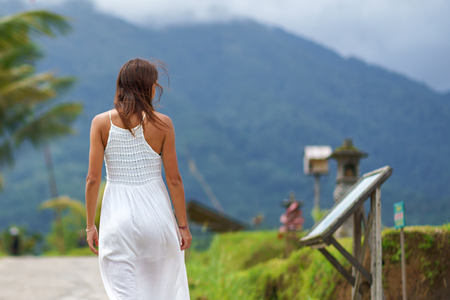 A tanned girl in a white dress walks forward on the road and look on a sign. The view from the back. In the background, a mountain in the fog. Close up