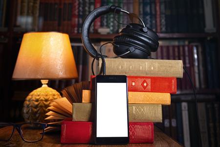 Handy, Kopfhörer und ein Stapel Bücher in der Nähe der Lampe. Konzept der Ausbildung und Hörbücher. Bücherregal der Bibliothek im Hintergrund. Schließen und kopieren. Attrappe, Lehrmodell, Simulation.