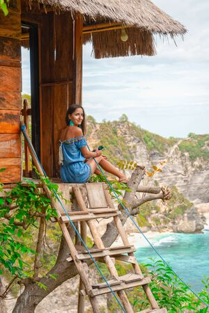 Beautiful young woman in swimwear relaxing while sitting in the tree house outdoors.