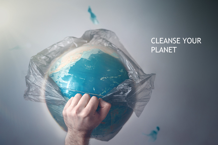 A man breaks a garbage bag which is wrapped globe of planet Earth. The concept of ecology and pollution of the surrounding environment. Tint and CLEANSE YOUR PLANET.