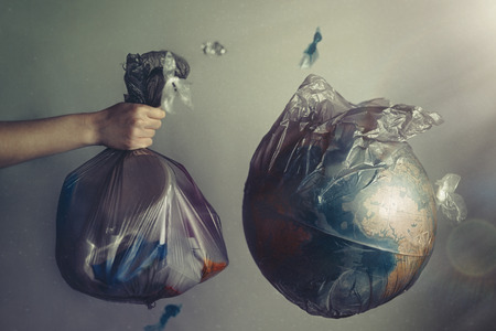 A womans hand holds a garbage bag next to the globe of planet Earth. Concept of ecology and environmental protection. The recycle sign. Dark tint.